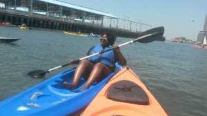 black plus size women kayaking on blue kayak