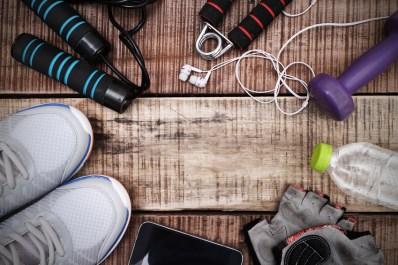 Sports equipment - sneakers, skipping rope, dumbbells, smartphone and headphones. Sport background on wooden floor, top view.
