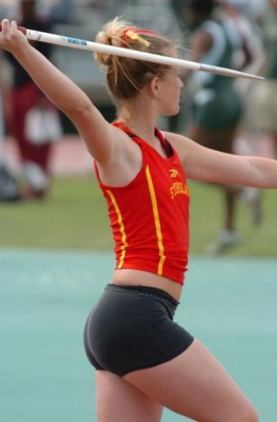 Sexy college girl in black tight shorts about to throw a javelin