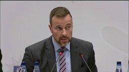 """Jan Hieber - Leiter der Soko """"Schwarzer Block"""" - spricht in Mikrophone."""