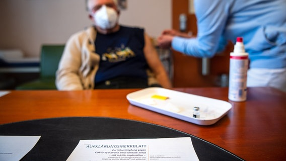 The Biontech / Pfizer vaccine education leaflet is on a doctor's office desk while a patient is being vaccinated.  © dpa-Bildfunk Photo: Sina Schuldt