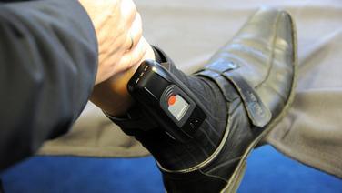 Elektronische Fußfessel an einem Bein © +++(c) dpa - Bildfunk+++ Fotograf: Carsten Rehder