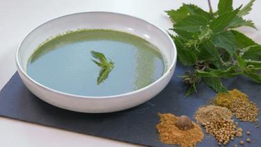 A deep plate of nettle soup on a slate plate.