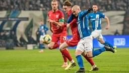 Zweikampf zwischen Niklas Kastenhofer (Hallescher FC) und Korbinian Vollmann (Hansa Rostock)
