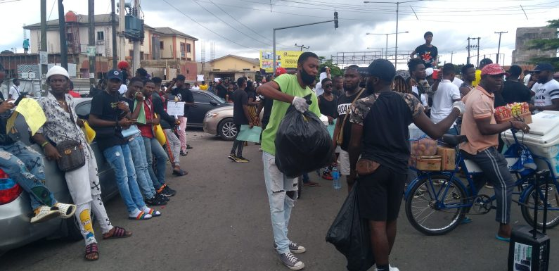 End SARS: Protester gathers empty cans, bottles, sachets, clean environment