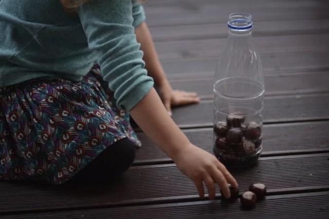 dziecko wrzuca kasztany do butelki