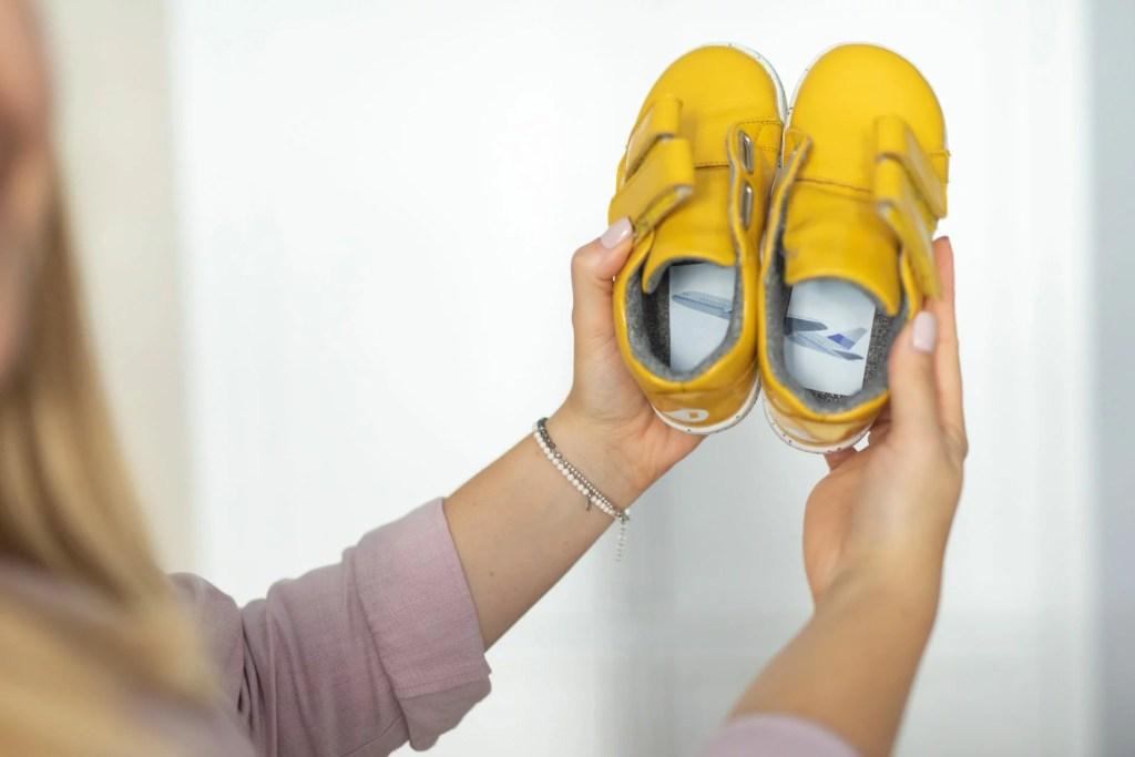 żółte buciki z przeciętą naklejką w środku