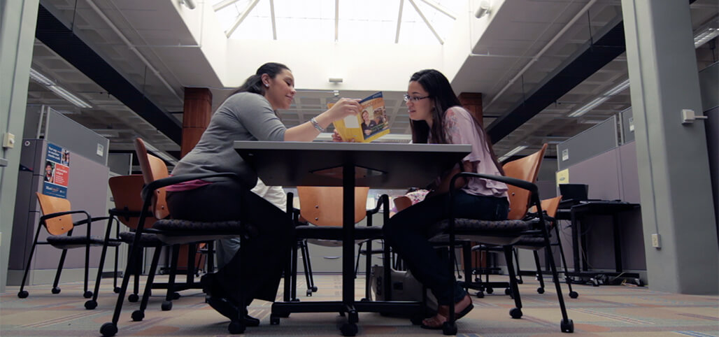 Two Students browsing through a brochure