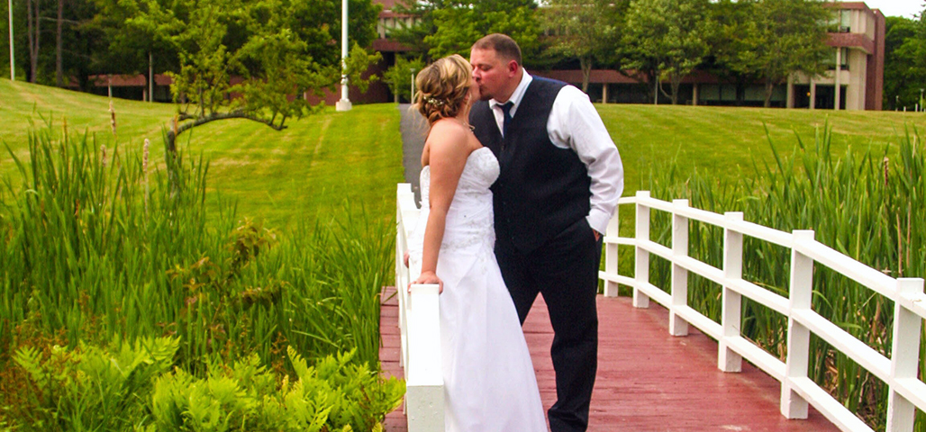 A bride and groom kis while standing on a small wodden bridge
