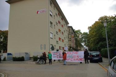 Wie ein Damoklesschwert hängt das GBG-Logo über den demonstrierenden Mietern | Foto: M. Schülke