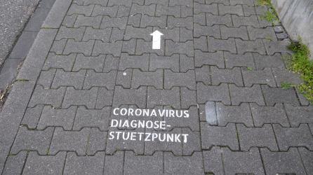 Auf den Boden aufgesprühte Markierungen, die den besten Weg von den Eingängen zum Corona Diagnose-Stützpunkt weisen   Foto: M. Schülke