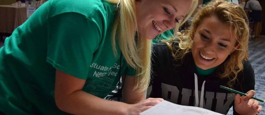 Teacher helping a high school student with a worksheet