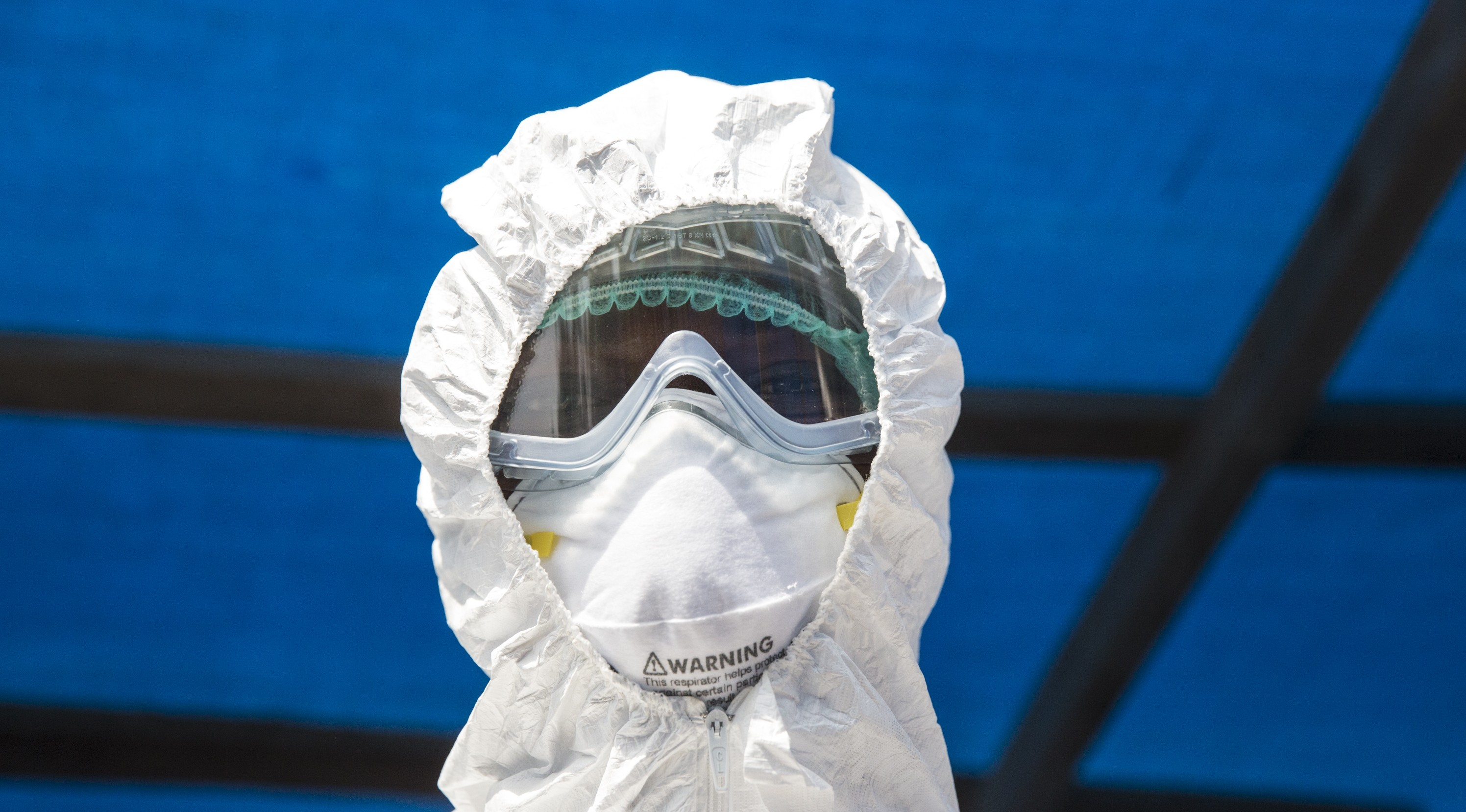 A lab technician is getting ready with his PPE to enter the Isolation ward of the government run hopital of Kabala, Sierra Leone to take blood sample from a suspected ebola case and will ensure the sample will either be flown by UN helicopter or driven to the capital as soon as possible. Photo by UNMEER/ Martine Perret. 18 December 2014
