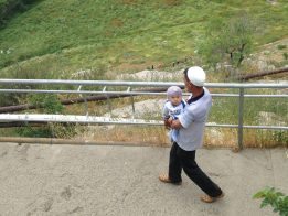 photo of a man in Southern Kyrgyzstan carrying a baby