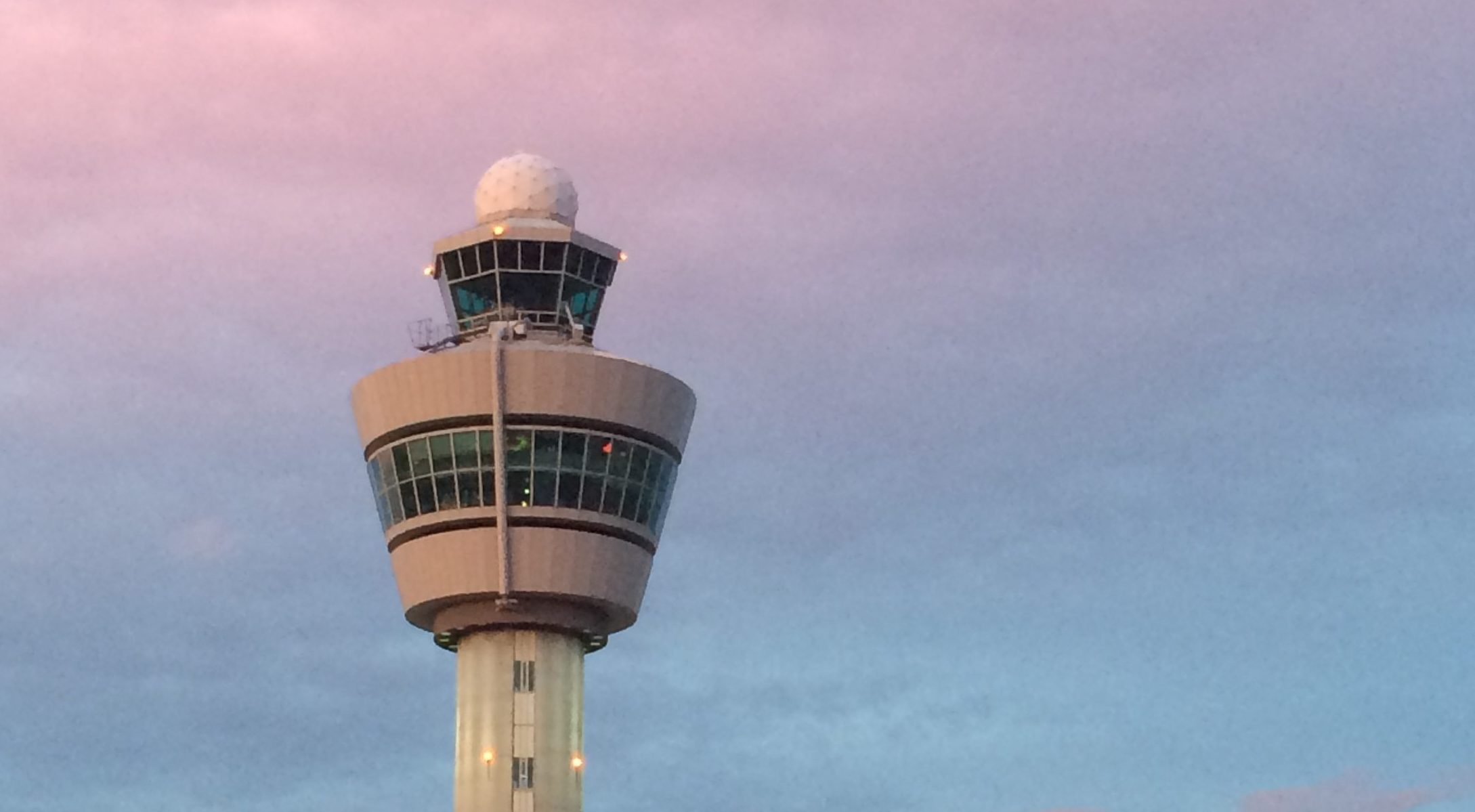 air traffic control tower in front of a pink and purple sky