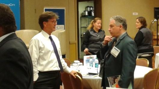 Ken Roberts (Izq.), presidente de WorldCity dialogando con un invitado.