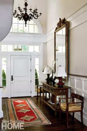 The high-ceilinged foyer is outfitted with antiques collected over the years.