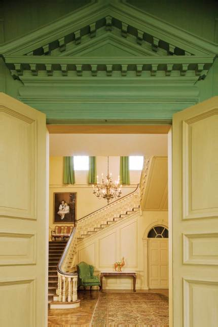 A pedimented doorway opens to the stair hall.