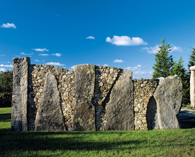 Large granite stones and small fieldstones combine to create a screen between the main house and a guest house.