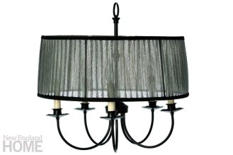 A wrap of iridescent metallic ribbon casts a warm glow on a multi-arm chandelier.