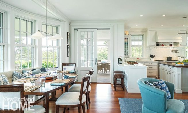 The spacious kitchen sports marble countertops and a custom dining table in a boat shape.