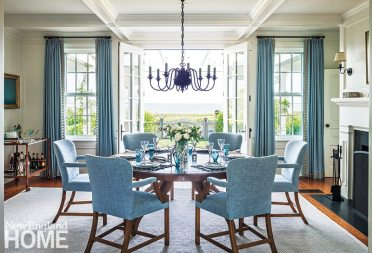 The sight line from the front door, through the dining room, and out to the sea is breathtaking. Designer Susan Reddick smartly played to the scenery with Lee Jofa linen drapes, a blue Stark carpet, and dining chairs clad in Brunshwig & Fils Oxford blue chenille.