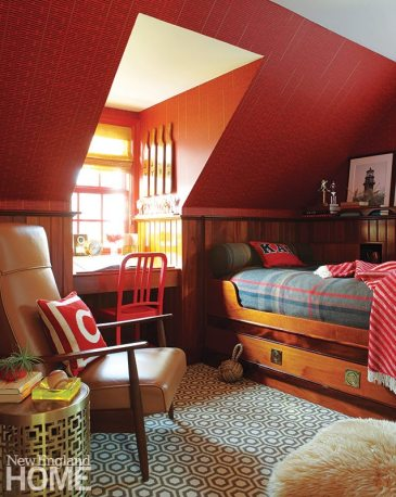 Deep red wallpaper above glossy paneling gives depth to the son's cozy room, and Bow added sophistication with the David Hicks geometric-patterned carpeting, a leather recliner, and a Jonathan Adler side table.