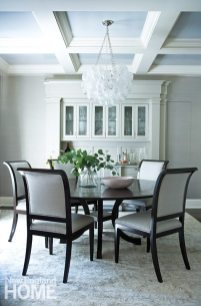 """A cluster of baubles hanging from the coffered ceiling and a console with scrollwork details elevate the dining room to what the homeowner calls the """"most beautiful room in the house."""""""