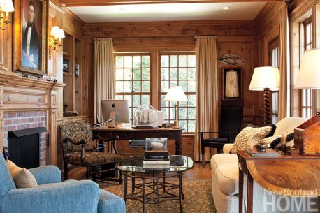 The husband's study, where much of his outstanding scrimshaw collection is showcased, is clad in reclaimed pine paneling. An antique portrait of a ship's captain hangs above the fireplace.