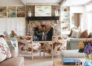 The designer combined bold texture with a serene color palette inspired by the coastline, picking up the tones of the fieldstone fireplace and the pickled beams. Objects collected from the sea (coral, shells, sea sponges) and the marine motif of the upholstery are reminders of the home's island location.