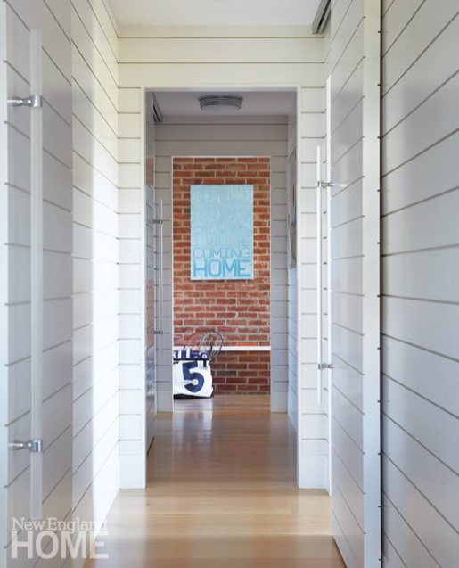Sliding barn doors open to a downstairs hallway that leads to the brick-walled mudroom.