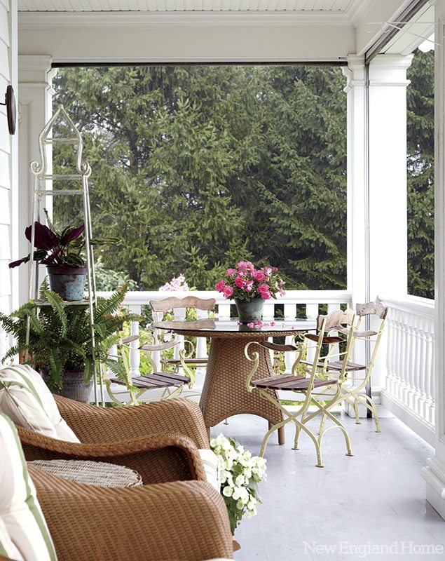 The porch is casually furnished with wicker and wrought iron.