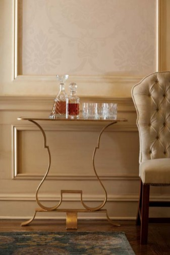 The brass-and-glass table's shape is a perfect match for the tufted dining chairs.