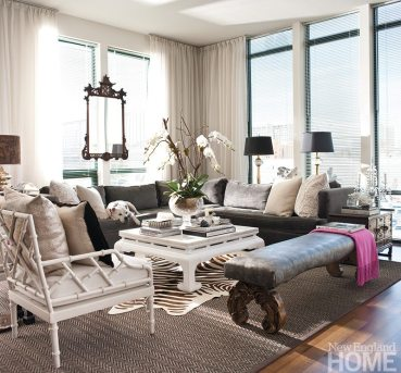 A sectional sofa and antique bench dominate the living room in Tiffany Eastman's Stamford apartment. Asian touches in the lacquered side table, metal bamboo chairs and a Chinese Chippendale mirror lend age and sophistication to the new space.