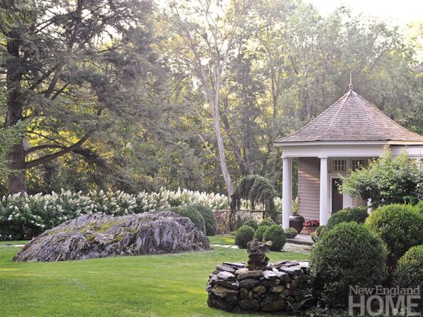 A weeping Norway spruce frames an entry gate, while dark trees help showcase a hedge of hydrangea paniculata.
