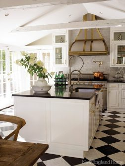 The centerpiece of the kitchen is the custom-designed brass-and-stainless stove hood.