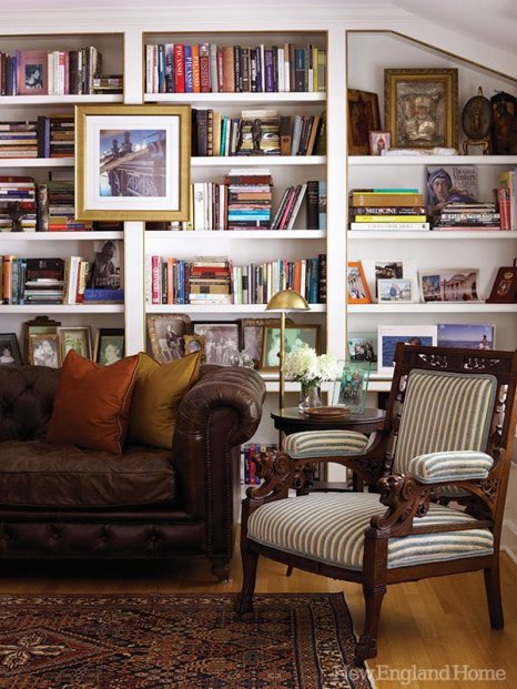 A leather Chesterfield sofa and an ornate nineteenth-century English walnut chair make a bold statement in the book-filled library.