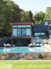 Guest quarters have a view through glass doors to the stone terrace and pool.
