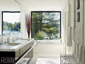 White marble and linens foster a sense of airiness and light in the master bath, which puts the focus on the surroundings, too, with its generous window.