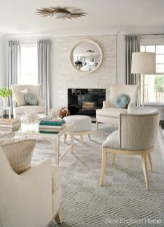 A calming palette of creams and blues envelops the living room, which gets a touch of extra drama from the glints of light bouncing off the starburst ceiling fixture and the convex mirror over the fireplace.