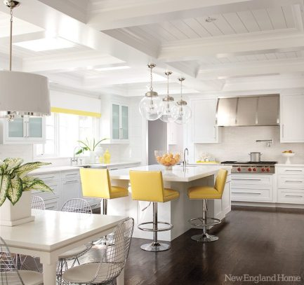 Chrome and yellow-vinyl barstools add sunny warmth to the modern kitchen, where skylights bring in natural light.