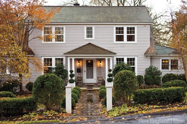 Trimmed hedges and topiary complement the Dutch colonial.