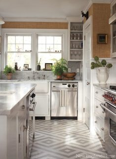 Ralph Lauren Home's Sudan Weave wallpaper wraps the kitchen above Carrara marble countertops. Decorative painter Topher Carnes executed the graphic floor.