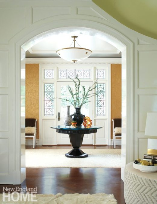 A new door with plenty of windows ushers light into the front foyer. Phillip Jeffries paper creates a golden glow.
