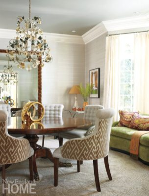 A chandelier brought from the owners' previous house is the dining room's focal point. The designer kept the overall palette neutral, adding punches of bright color.