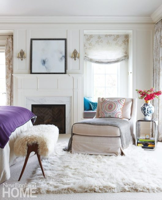 The fireplace and window seats were added when the large bedroom was converted to dressing rooms, a bath, a sitting room, and this cozy sleeping area, where pops of blue and purple dress up a background of lilac-tinted pale gray.
