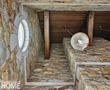 The architect enclosed what had been an open connection to the garage, incorporating beams and stones to create a lofty secondary entry the family uses regularly.