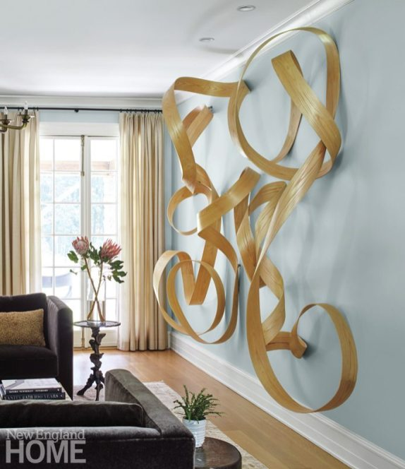 On the living room wall, an abstract wood sculpture by Jeremy Holmes nods to the fluid movement of the home's central staircase and railing.