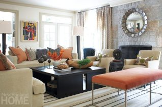 A custom carpet from J.D. Staron grounds the warm, bright family room, where designer Carey Karlan made use of luxurious fabrics, such as creamy Holly Hunt chenille on the Ralph Lauren sofas, a cotton-mohair blend from Schumacher on the bench, and taupe leather on the Lee Industries armchairs. The midcentury painting by Irene Zevon is one of several in the owners' collection.