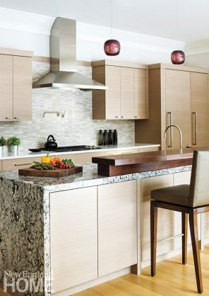 The open-plan kitchen boasts custom-made striated ash veneer cabinets and a walnut-topped granite island.